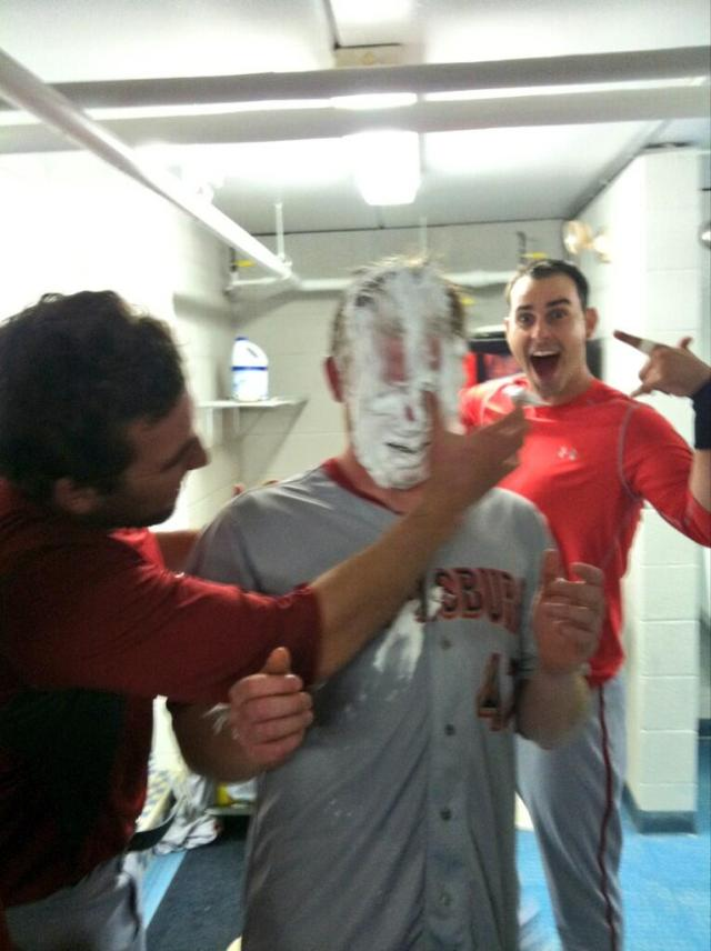Nate Karns delivers the shaving cream pie to the face of Paul Demny while Jimmy VanOstrand photobombs the proceedings Photo courtesy @aaronbarrett30